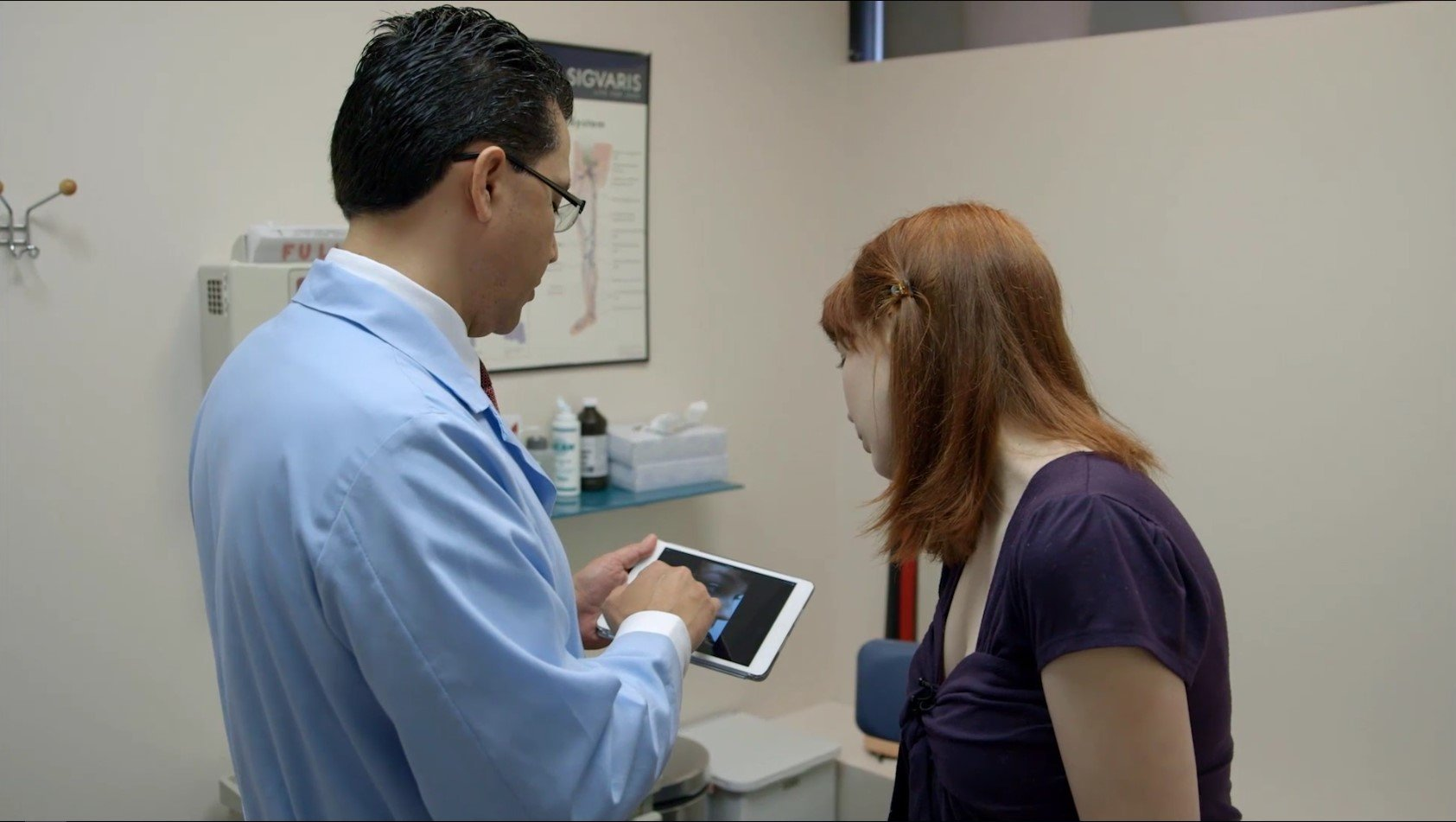 Doctor with patient showing patient photos on iPad